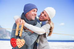 Composite image of attractive couple hugging on the beach in warm clothing Royalty Free Stock Images