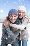 Composite image of attractive couple hugging and smiling at camera on the beach in warm clothing Royalty Free Stock Images