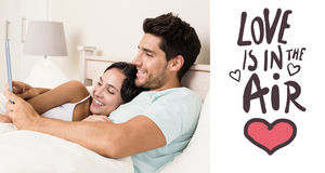 Composite image of attractive couple lying in bed with tablet pc. Attractive couple lying in bed with tablet pc against love is in the air Stock Photos