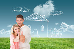Composite image of attractive couple showing thumbs up to camera. Attractive couple showing thumbs up to camera against blue sky over green field Stock Image