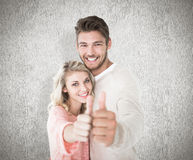 Composite image of attractive couple showing thumbs up to camera Royalty Free Stock Photography