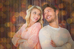 Composite image of attractive couple smiling with arms crossed Stock Photos