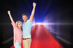 Composite image of attractive couple smiling and cheering Royalty Free Stock Photo