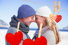 Composite image of attractive couple smiling at each other on the beach in warm clothing Stock Images