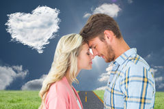 Composite image of attractive couple standing touching heads Stock Photo