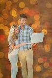 Composite image of attractive couple standing and using laptop Royalty Free Stock Photos