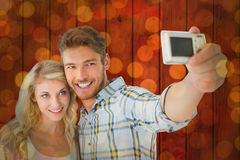 Composite image of attractive couple taking a selfie together Royalty Free Stock Photos