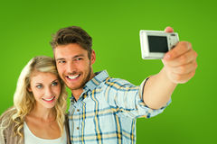 Composite image of attractive couple taking a selfie together Royalty Free Stock Images