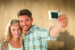 Composite image of attractive couple taking a selfie together Stock Images