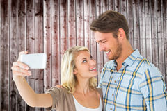 Composite image of attractive couple taking a selfie together Royalty Free Stock Image