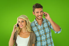 Composite image of attractive couple talking on their smartphones Stock Photos
