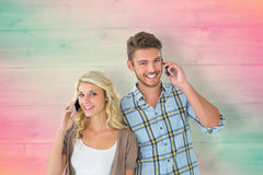Composite image of attractive couple talking on their smartphones Stock Images