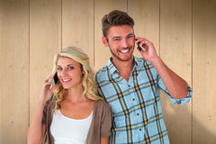 Composite image of attractive couple talking on their smartphones Royalty Free Stock Image