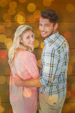 Composite image of attractive couple turning and smiling at camera Royalty Free Stock Images