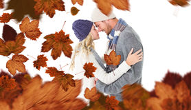Composite image of attractive couple in winter fashion hugging Royalty Free Stock Image