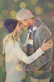 Composite image of attractive couple in winter fashion hugging Royalty Free Stock Images