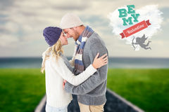 Composite image of attractive couple in winter fashion hugging Royalty Free Stock Photos