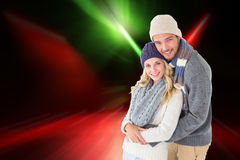 Composite image of attractive couple in winter fashion hugging Stock Photos