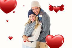 Composite image of attractive couple in winter fashion hugging Royalty Free Stock Photography