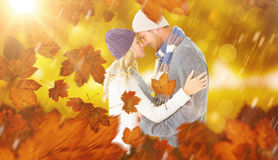Composite image of attractive couple in winter fashion hugging Stock Photo