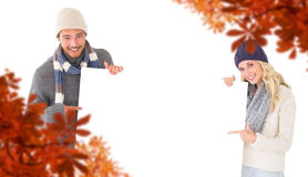 Composite image of attractive couple in winter fashion showing poster Stock Photography