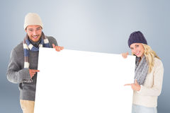 Composite image of attractive couple in winter fashion showing poster Royalty Free Stock Image