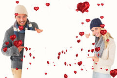 Composite image of attractive couple in winter fashion showing poster Royalty Free Stock Photography