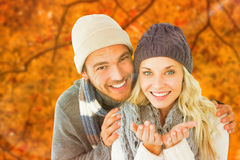 Composite image of attractive couple in winter fashion smiling at camera Royalty Free Stock Images