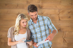 Composite image of attractive couple working out their finances Royalty Free Stock Photography