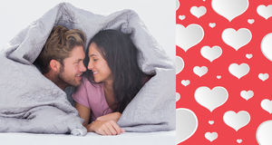 Composite image of attractive couple wrapped in the duvet Stock Photos