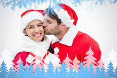 Composite image of attractive festive man giving girlfriend a kiss and present Royalty Free Stock Photos