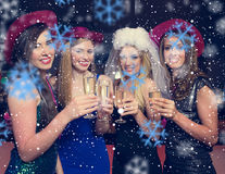 Composite image of attractive friends clinking champagne glasses at hen night. Attractive friends clinking champagne glasses at hen night against snowflakes Stock Photography