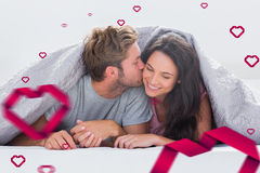 Composite image of attractive man kissing his wife Royalty Free Stock Image