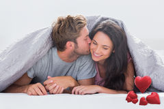 Composite image of attractive man kissing his wife Royalty Free Stock Photos