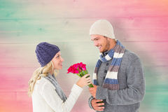 Composite image of attractive man in winter fashion offering roses to girlfriend Stock Images