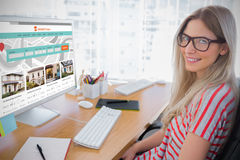Composite image of attractive photo editor working on computer. Attractive photo editor working on computer against composite image of property web site royalty free stock image
