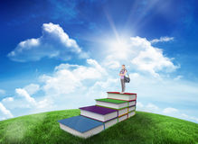 Composite image of attractive student holding books and her bag while standing Stock Photography