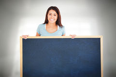 Composite image of attractive woman holding a  board. Attractive woman holding a  board against room overlooking city Royalty Free Stock Photo