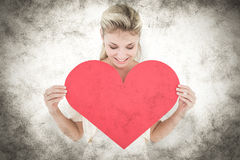 A Composite image of attractive young blonde showing red heart Royalty Free Stock Photo