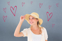 Composite image of attractive young blonde smiling in sunhat Royalty Free Stock Image