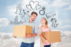 Composite image of attractive young couple carrying moving boxes Royalty Free Stock Photos