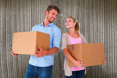 Composite image of attractive young couple carrying moving boxes Royalty Free Stock Photo