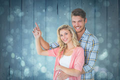 Composite image of attractive young couple embracing and pointing Stock Image