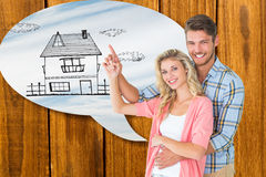 Composite image of attractive young couple embracing and pointing Stock Photo