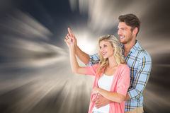 Composite image of attractive young couple embracing and pointing Royalty Free Stock Image