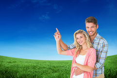 Composite image of attractive young couple embracing and pointing Royalty Free Stock Photo
