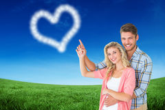 Composite image of attractive young couple embracing and pointing Royalty Free Stock Photography