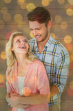 Composite image of attractive young couple embracing and smiling. Attractive young couple embracing and smiling against close up of christmas lights Stock Image
