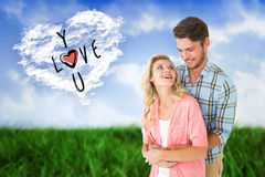 Composite image of attractive young couple embracing and smiling. Attractive young couple embracing and smiling against cloud heart Royalty Free Stock Photography