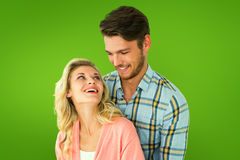 Composite image of attractive young couple embracing and smiling. Attractive young couple embracing and smiling against green vignette Stock Image
